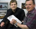 [photo]MP Angus Robertson, left, hands over a petition about broadband for Dufftown resident Leslie Craib to sign.